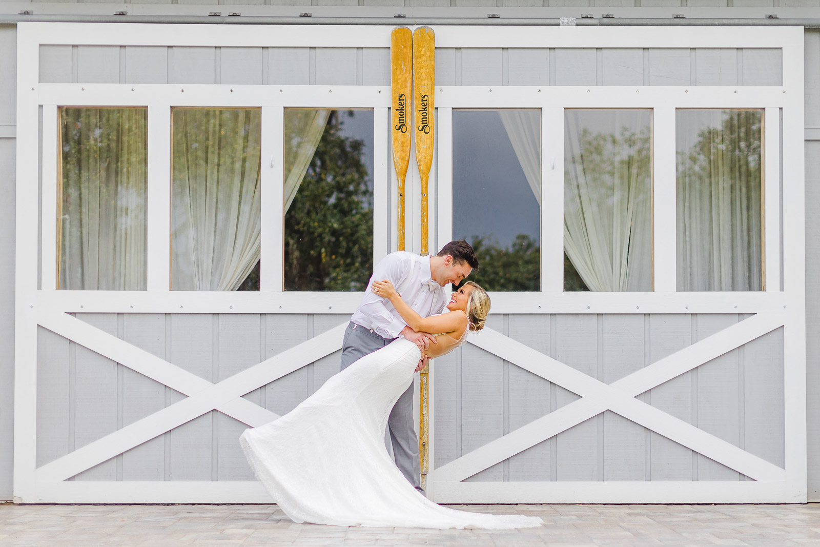 Groom dipping bride in front of barn doors at Up the Creek Farms