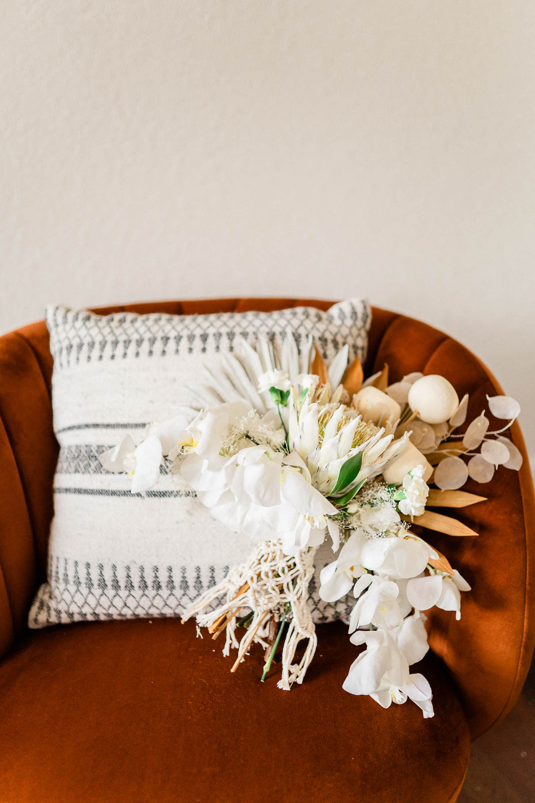 boho inspired neutral toned bridal bouquet on burnt orange chair