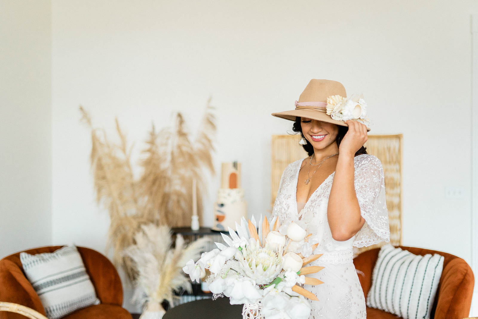 Bride will large brimmed hat holding white bouquet