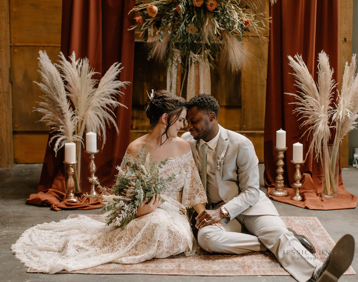bride and groom sitting on rug with boho backdrop