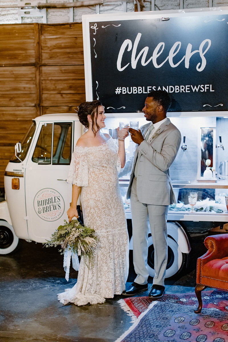bride and groom toasting in front of mobile wedding bar
