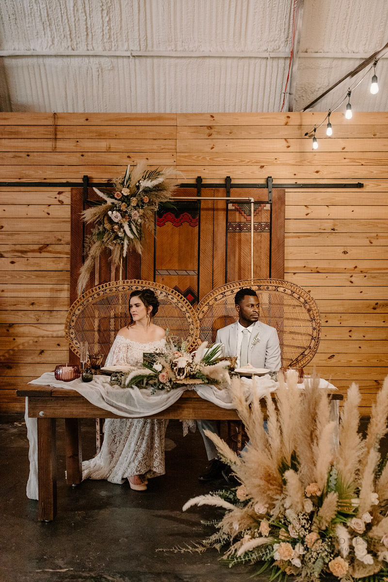 bride and groom sitting in peacock chair at sweetheart table