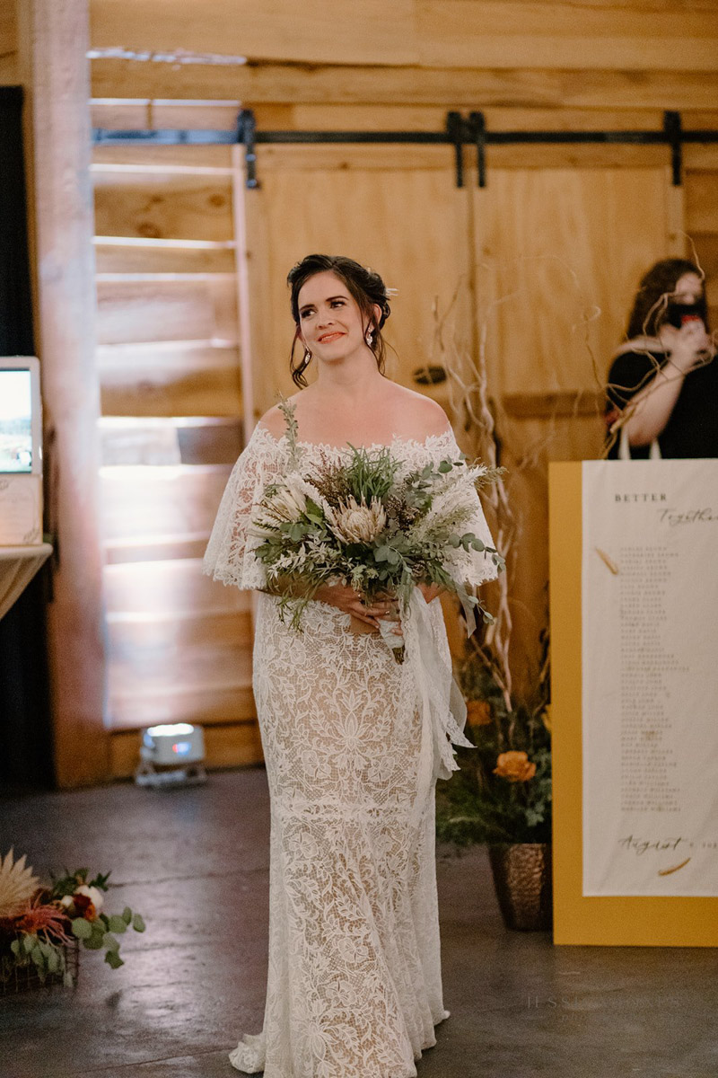 Bride holding rustic boho wedding bouquet walking up the aisle for vow renewal