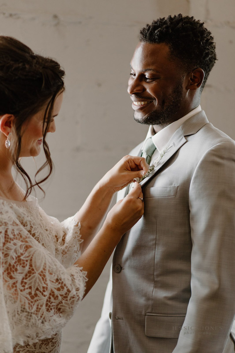 Bride in Boho Gown pinning boutonniere on groom