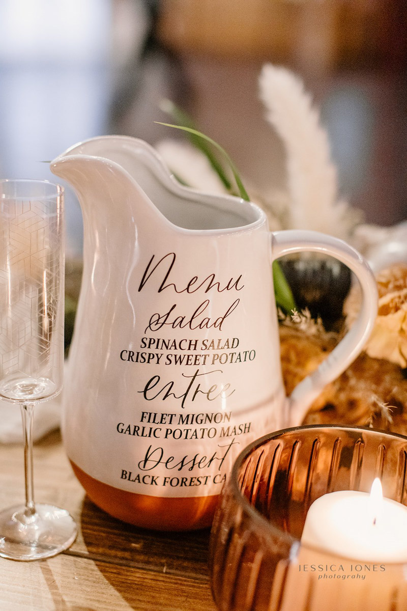 White pitcher with wedding dinner menu on sweetheart table