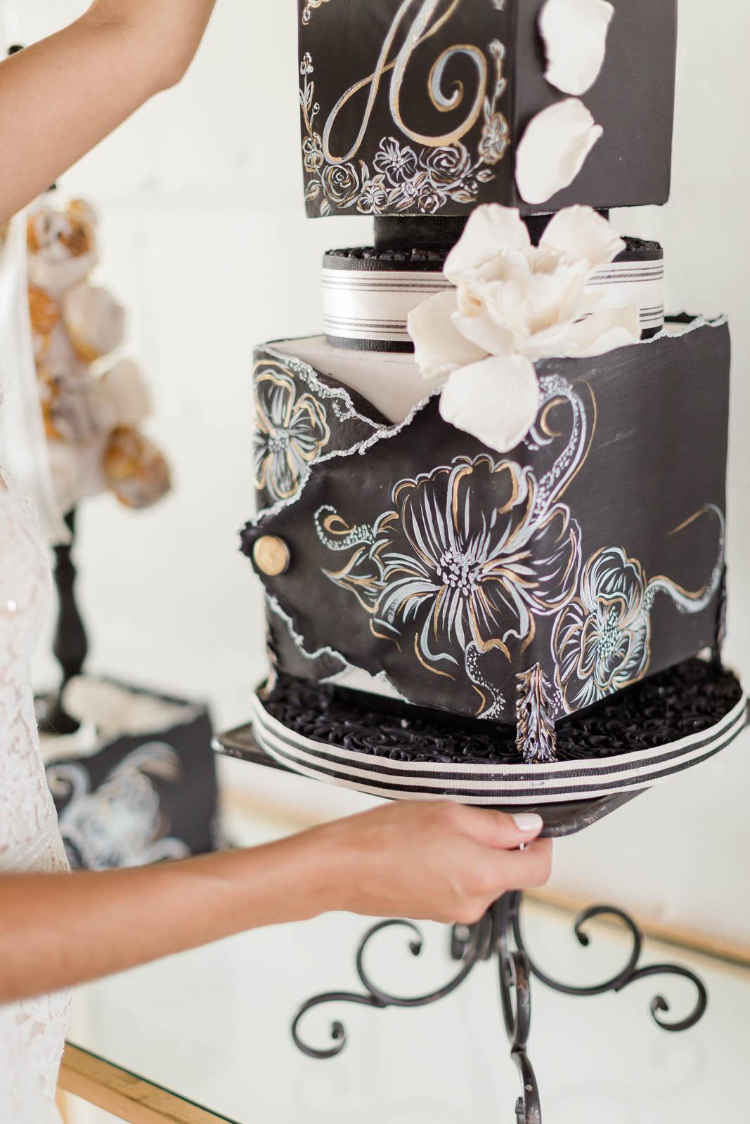 Bride holding hand painted black wedding cake