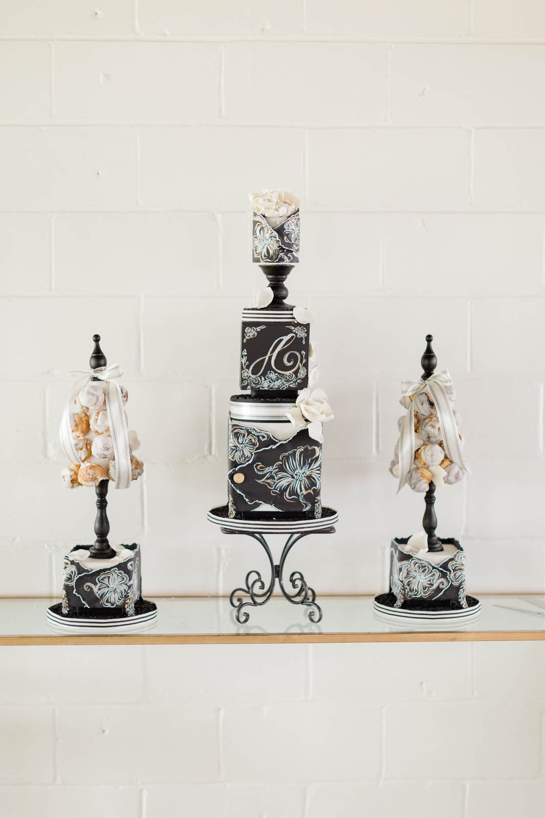 Three tiered black and white wedding cake with smaller wedding cakes next to it