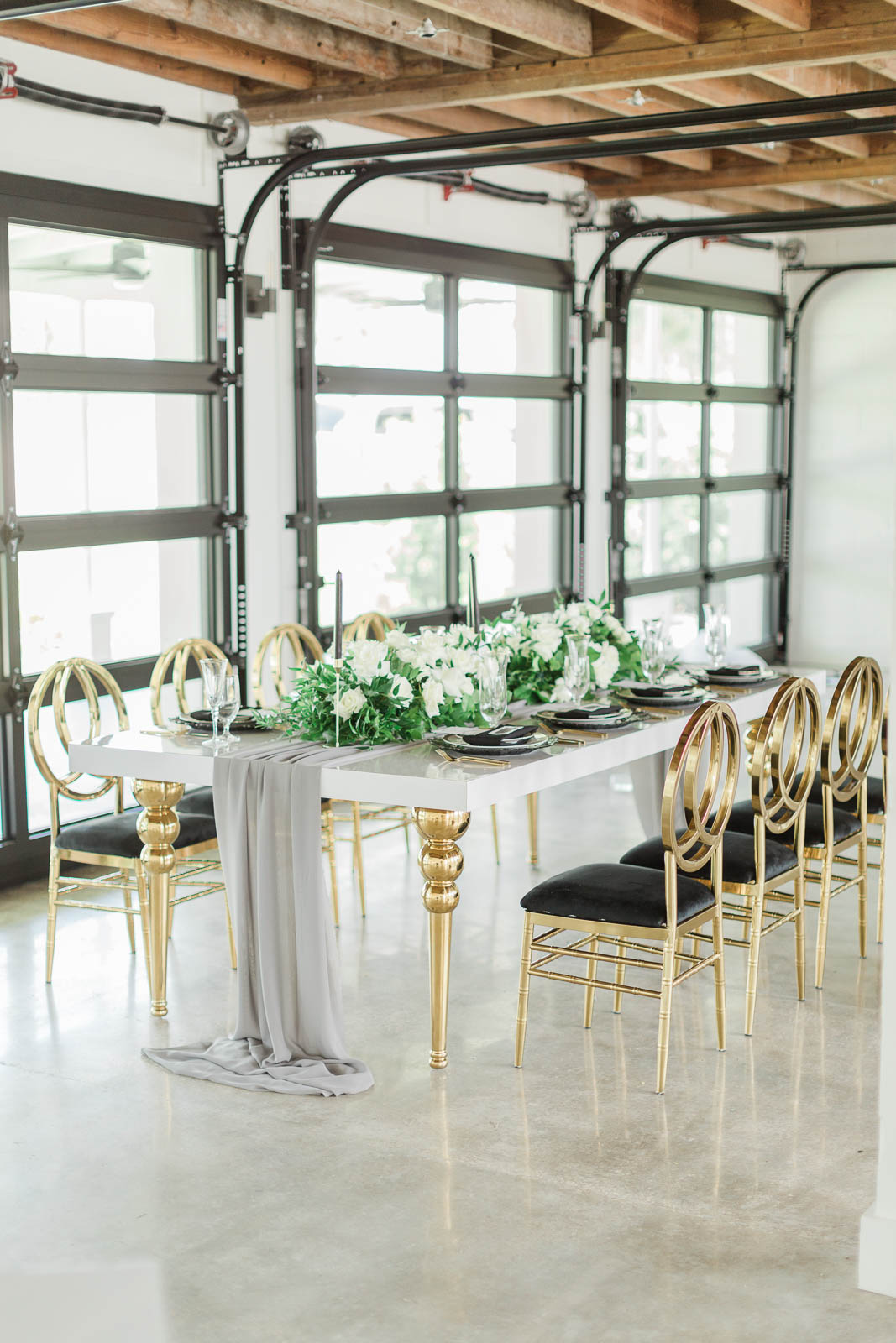 Reception table with gold chairs and white and greenery centerpieces