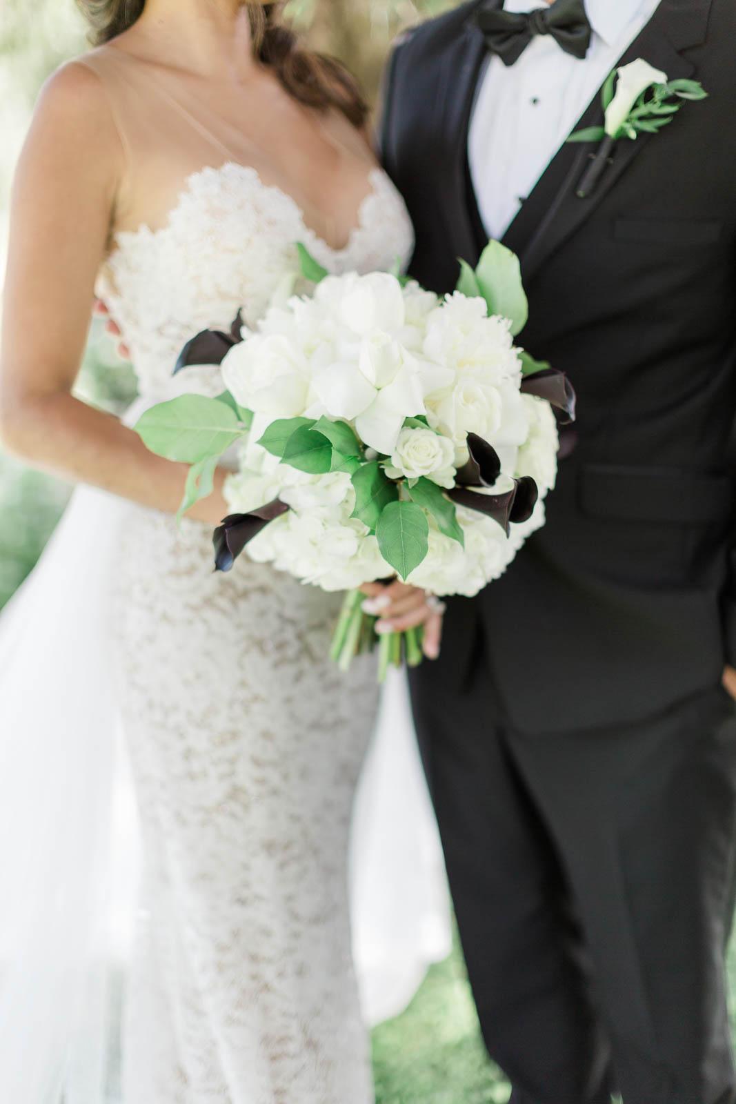 Bride holding white hydrangea bouquet with dark purple calla lilies.