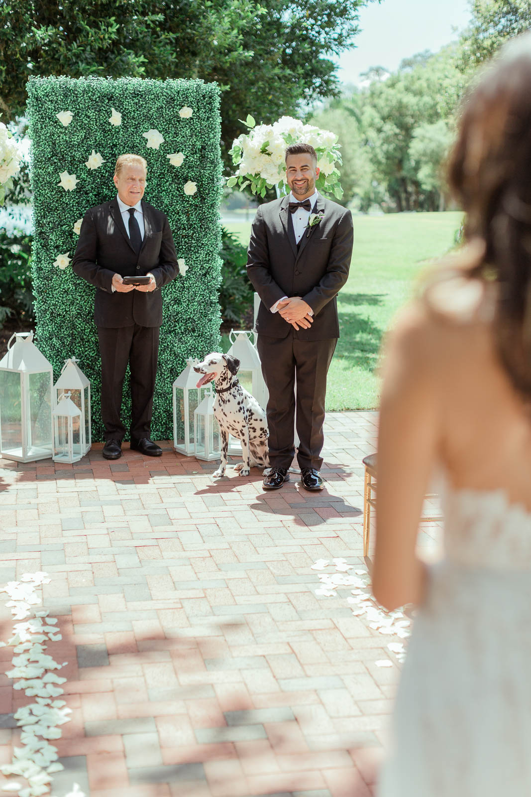 Groom and officiant watching bride walk down the aisle.