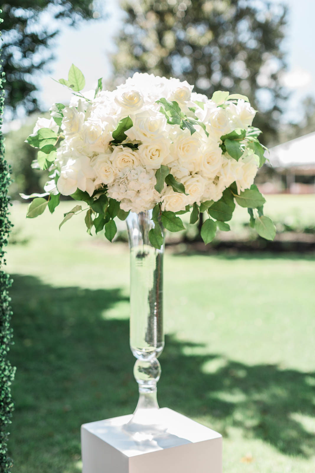 large floral arrangement with white roses and hydrangeas in tall glass vase.